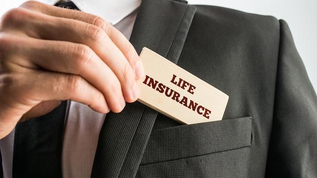 Close-up van de hand van een zakenman die een kaartlezing - levensverzekering - weergeeft terwijl hij deze uit de zak van zijn jas in een conceptueel beeld verwijdert