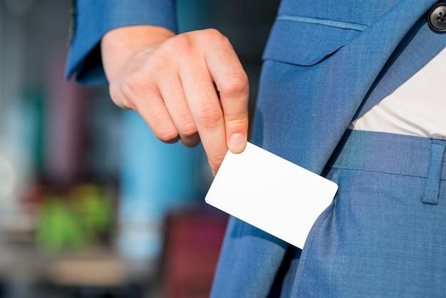 Close-up van de hand van een zakenman die lege witte kaart uit zak verwijdert