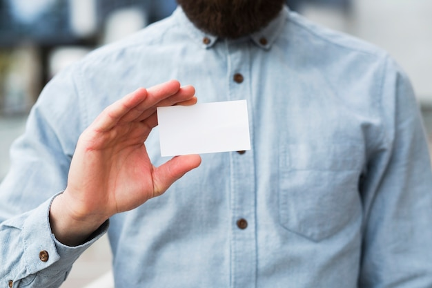 Close-up van de hand van een zakenman die wit leeg visitekaartje toont