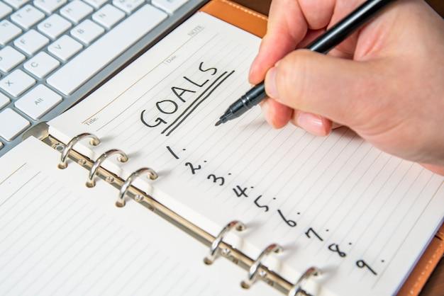 Close-up van de hand van een zakenman het schrijven doelstellingen en lijst in het dagboek.