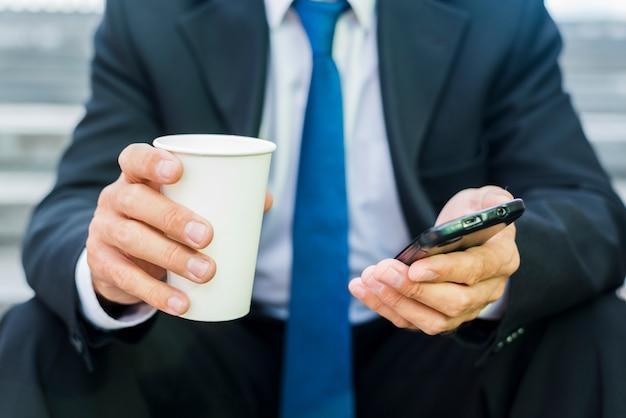 Close-up van de hand van een zakenman met een kopje koffie en mobiele telefoon