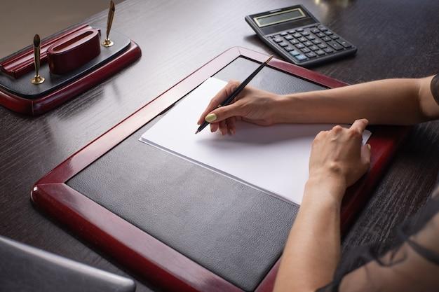 Close-up van de hand van een zakenvrouw die op papieren boven het bureau tekent