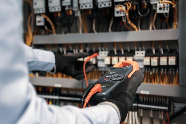 Close-up van de hand van elektrotechnisch ingenieur met behulp van meetapparatuur om de elektrische stroomspanning op de stroomonderbreker te controleren
