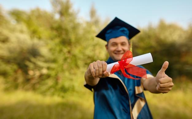 Close-up van de hand van graduate stak zijn handen omhoog en viert met certificaat in handen en voelt zich zo gelukkig op de startdag, education success concept