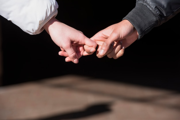 Close-up van de hand van het paar die elkaars vingers houden