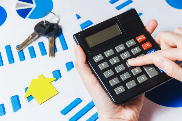 Close-up van de hand van het vrouwelijke gebruikend calculator met document huismodel op bureau met diagram.