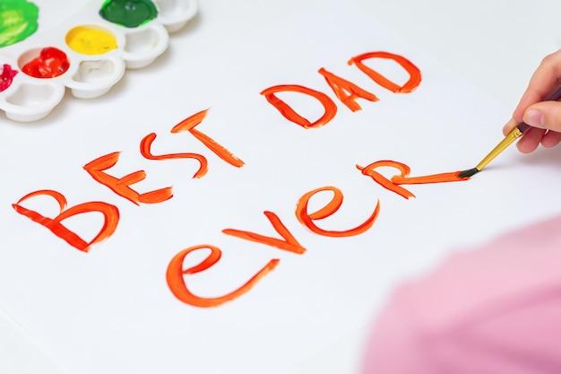 Close-up van de hand van kind handgeschreven tekst beste vader ooit tekenen door aquarellen op wit papier. vaderdag en familie concept.