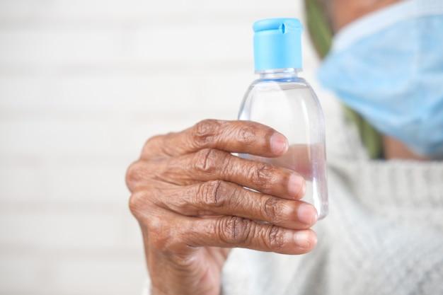 Close-up van de hand van oudere vrouwen met behulp van ontsmettingsgel om virussen te voorkomen
