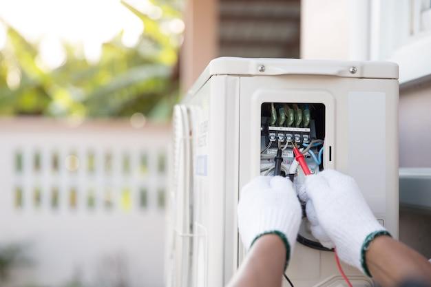 Close-up van de hand van technicus met behulp van meten om de elektrische stroomspanning op de stroomonderbreker op de buitenluchtcompressoreenheid te controleren.