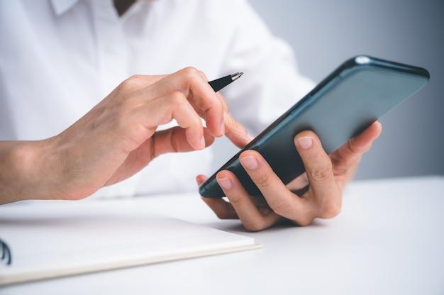 Close-up van de hand van vrouwen met behulp van mobiele telefoon of mobiel voor zoekwebsite, gegevens, sociaal netwerk met communicatie. bedrijfs- en financieel concept.