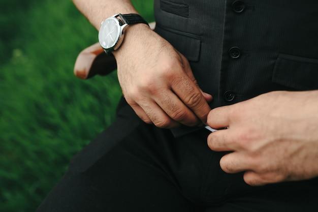 Close-up van de handen dichtknopen van een vest