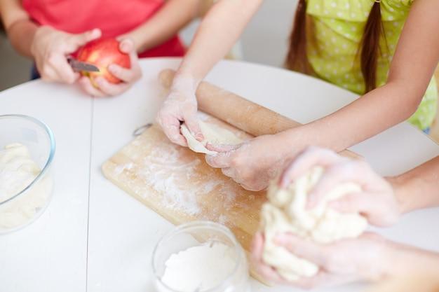 Close-up van de handen die deeg voorbereiden basis voor pizza's