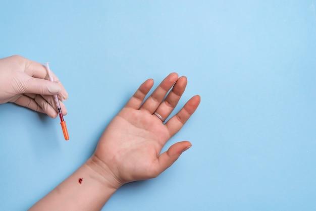 Close-up van de handen die van de verpleegster een bloedmonster nemen