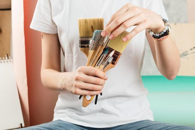 Close-up van de handen die van de vrouw en diverse verfborstels houden plukken