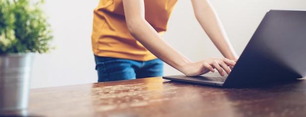 Close-up van de handen die van de vrouw op laptop computer en het zoeken web typen