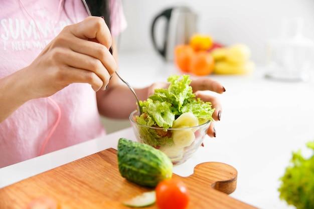 Close-up van de handen die van de vrouw salade in de keuken mengen