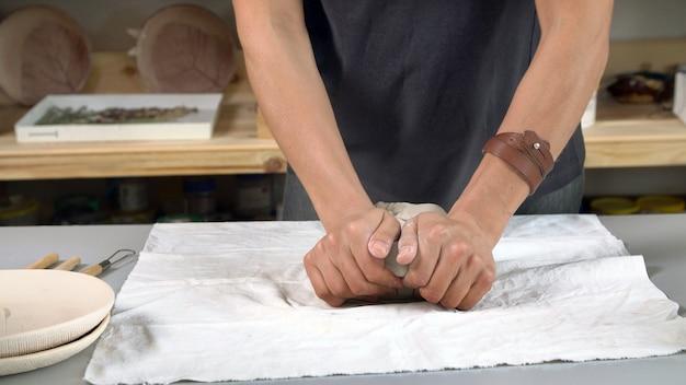 Close-up van de handen die van vrouwen klei voor aardewerk kneden