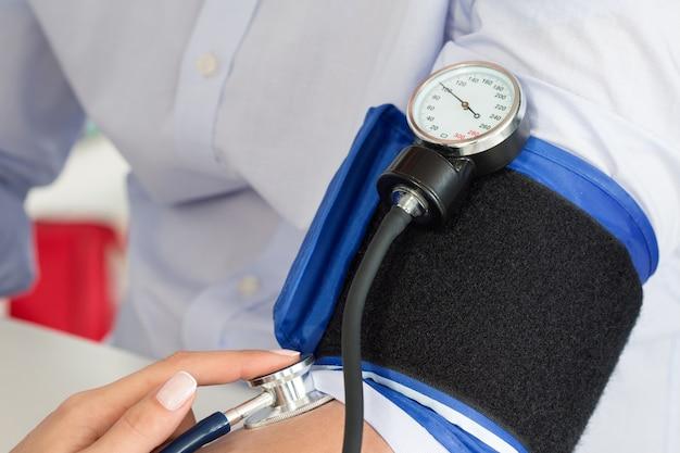 Close-up van de handen van de arts die de bloeddruk meet aan haar mannelijke patiënt. gezondheidszorg en medisch concept