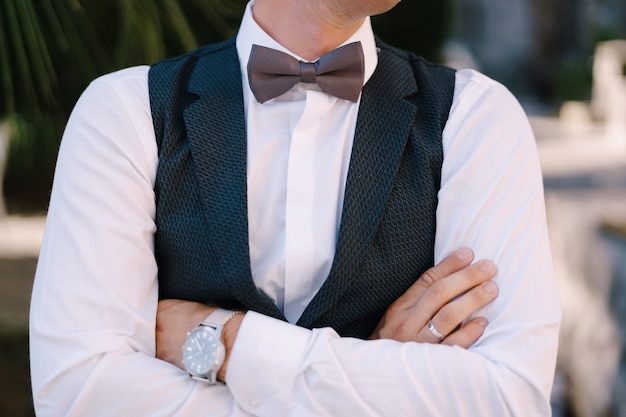 Close-up van de handen van de bruidegom die op zijn borst worden gevouwen