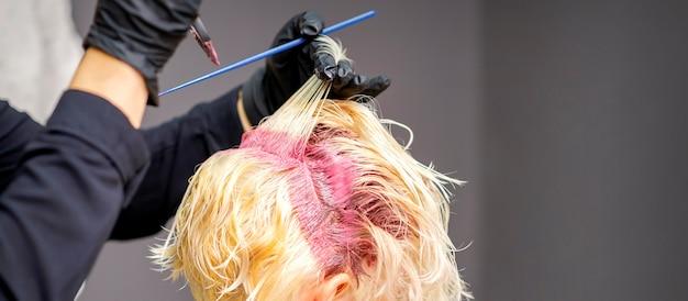 Close-up van de handen van de kapper roze kleurstof toe te passen op het blonde haar van de vrouw in een kapsalon