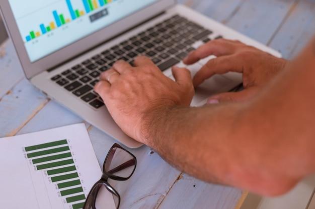 Close-up van de handen van de man die een laptop gebruikt - zakenman die naar de grafieken op het scherm en op de tafel kijkt