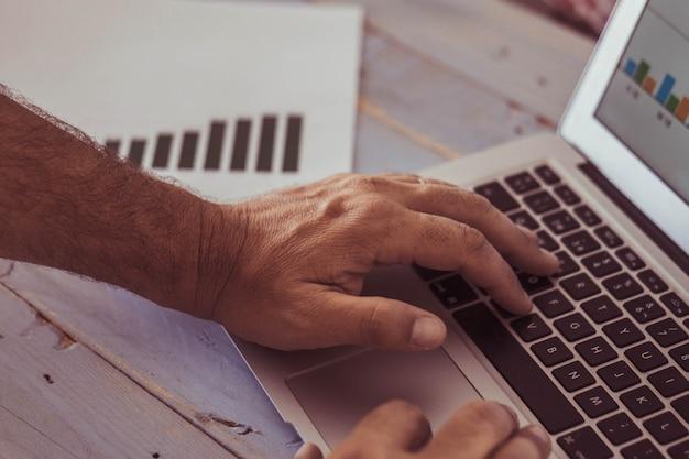 Close-up van de handen van de man die in een laptop typt en naar de grafieken op het scherm en op de tafel kijkt - portret of werkende man