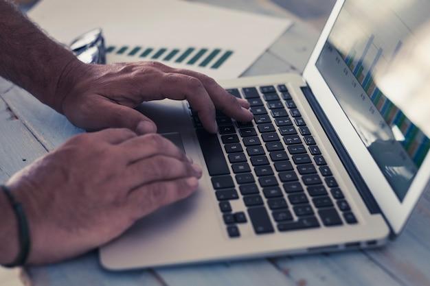 Close-up van de handen van de man op een laptop die hard werkt om een agenzy te creëren - zakenman met afbeeldingen op kantoor of thuis