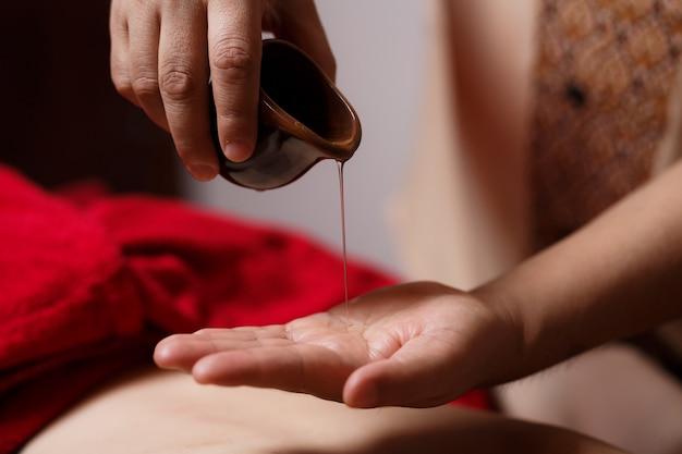 Close-up van de handen van de masseur stroomt een druppel massageolie langs zijn hand