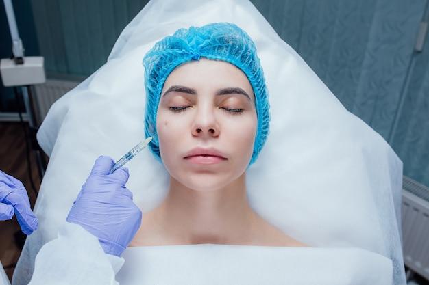Close up van de handen van de schoonheidsspecialiste expert botox injecteren in vrouwelijk voorhoofd