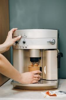 Close-up van de handen van de vrouw die een kop van koffie zetten
