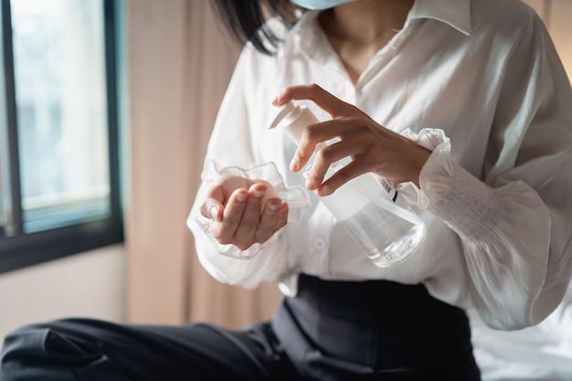 Close-up van de handen van de vrouw met behulp van de dispenser voor handdesinfecterende gel, tegen 2019-ncov thuis.