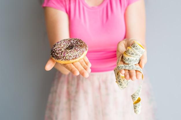 Close-up van de handen van de vrouw met een donut en een meetlint. het concept van gezond eten. eetpatroon.