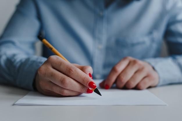 Close-up van de handen van de vrouw met rode nagels die documenten ondertekenen en corrigeren aan de balie