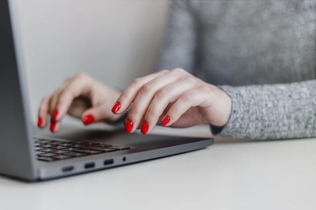 Close-up van de handen van de vrouw met rode nagels op het grijze laptop toetsenbord.