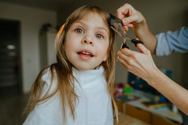 Close-up van de handen van de vrouwelijke moeder knippen haar van haar vier jaar oude dochter thuis in de kinderkamer. thuis dagelijkse routine.