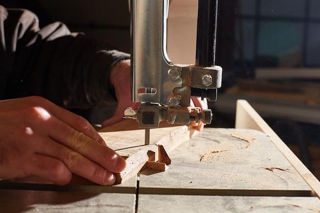Close-up van de handen van een arbeider die houten raad op een lintzaag zaagt