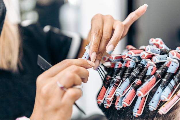 Close-up van de handen van een blanke kapper die het haar van een klant repareert met rollers om het te verven