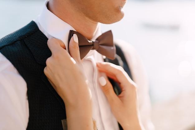Close-up van de handen van een bruid die een vlinderdas aan de bruidegom zetten