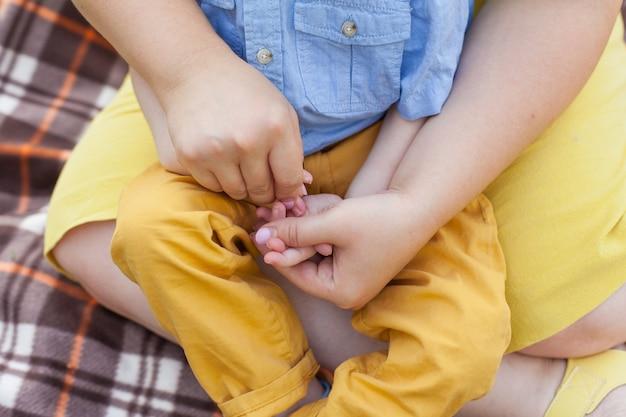 Close-up van de handen van een gehandicapt kind en zijn moeder die ladushki speelt. infantiele hersenverlamming. inschakelen. onbekwaamheid