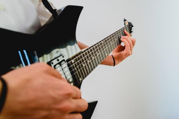 Close-up van de handen van een gitarist die een lied uitvoert terwijl het drukken van de snaren.