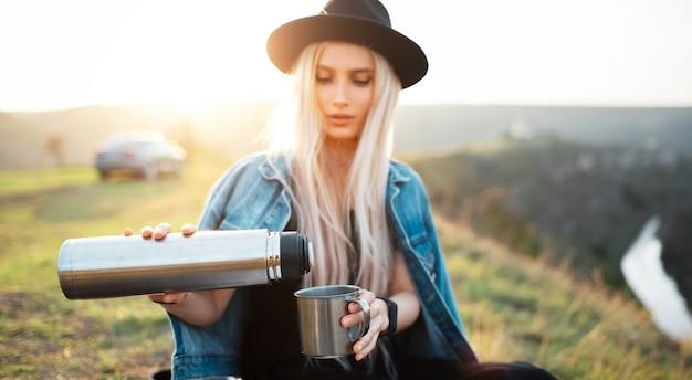 Close-up van de handen van een jong meisje dat thee uit een thermoskan naar een stalen mok giet op de achtergrond van de zonsondergang.