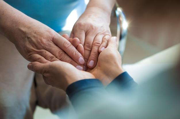 Close-up van de handen van een jonge en oude vrouw. het concept van hulp en ondersteuning voor ouderen.
