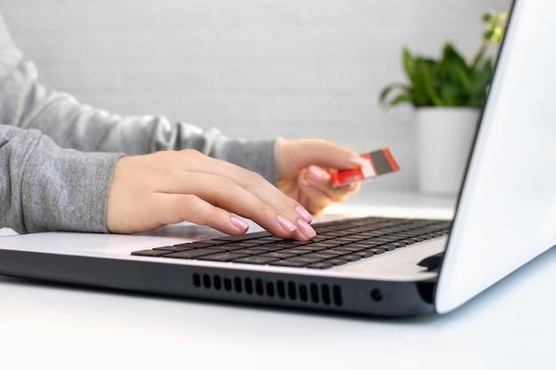 Close-up van de handen van een jonge vrouw die een creditcard vasthoudt en een laptop gebruikt