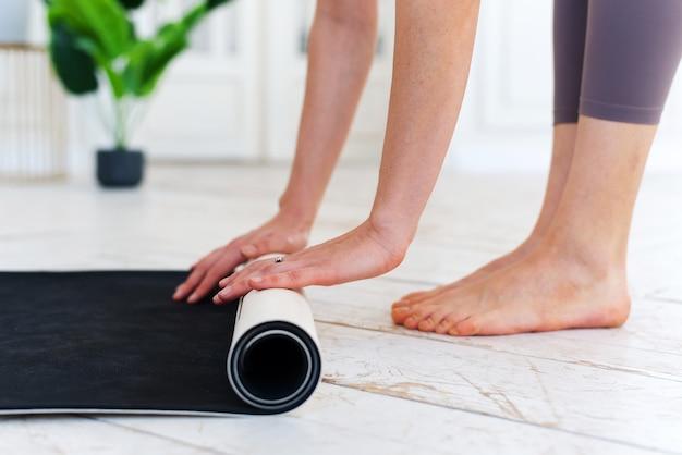 Close-up van de handen van een jonge vrouw die een grijze yoga- of fitnessmat vouwen na het sporten thuis of in de sportschool. yoga, sport, gezond levensstijlconcept.