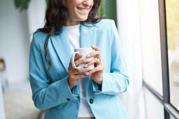 Close-up van de handen van een jonge vrouw die onherkenbaar is in formele kleding met een kopje koffie voor haar...