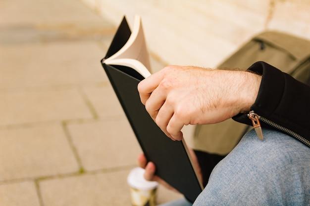 Close-up van de handen van een jongen die een boek op straat leest. lifestyle, lezen en persoon concept.