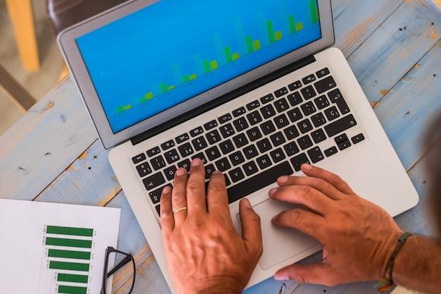 Close-up van de handen van een man die op zijn laptop typt en naar een aantal statistieken van zijn werk kijkt - blauwe houten tafel