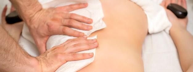 Close-up van de handen van een masseur met handdoekmassage