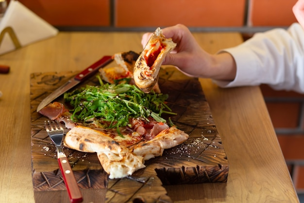 Close-up van de handen van een meisje dat bruschetta of pizza eet met kruiden en saus in een café