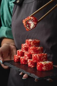Close-up van de handen van een meisje houdt sushi en de broodjes van californië op een zwarte steen. japanse traditionele keuken.
